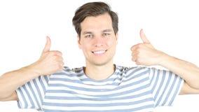 ung attraktiv stilig man som gör en gest upp tummar Fotografering för Bildbyråer