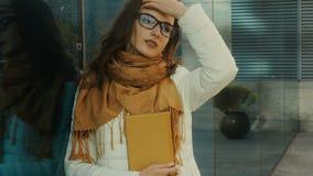 Ung attraktiv student i exponeringsglas med böcker i händer arkivfilmer