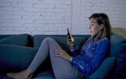 Ung attraktiv 20-talkvinna som ligger på den hem- soffasoffan genom att använda internet på koncentrerad och kopplad av app-böjel Arkivbild
