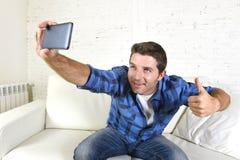 Ung attraktiv 30-talman som tar selfiebilden eller självvideoen med hemmastatt sammanträde för mobiltelefon på att le för soffa s Arkivfoton