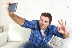 Ung attraktiv 30-talman som tar selfiebilden eller självvideoen med hemmastatt sammanträde för mobiltelefon på att le för soffa s Arkivbild