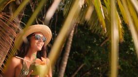 Ung attraktiv turist- flicka för blandat lopp som dricker nytt thailändskt kokosnötvatten på den tropiska stranden 4K som är slow arkivfilmer