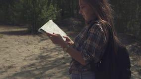 Ung attraktiv turist- kvinna med ryggsäcken som kontrollerar med hennes översikt och ser aroiund på lokal terräng Kameran är lager videofilmer