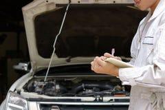 Ung auto mekaniker i enhetlig handstil på skrivplattan mot bilen i öppen huv på reparationsgaraget Begrepp för underhållsservice arkivbild
