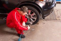 Ung auto mekaniker som kontrollerar lufttrycket av ett däck Royaltyfri Foto