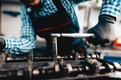 Ung auto mekaniker Twists en mutter Tjänste- station arkivfoto