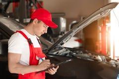 Ung automatisk mekaniker med skrivplattan nära bilen i servicemitt royaltyfria foton