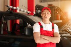 Ung automatisk mekaniker nära bilen i servicemitt royaltyfria foton