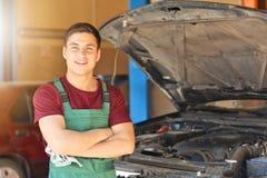 Ung automatisk mekaniker nära bilen i servicemitt arkivbilder
