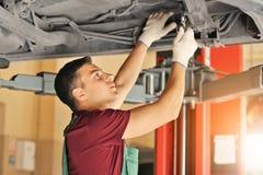 Ung automatisk mekaniker som reparerar bilen i servicemitt royaltyfri foto