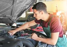 Ung automatisk mekaniker som reparerar bilen i servicemitt fotografering för bildbyråer