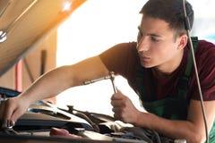 Ung automatisk mekaniker som reparerar bilen i servicemitt arkivbilder