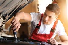 Ung automatisk mekaniker som reparerar bilen i servicemitt royaltyfria foton
