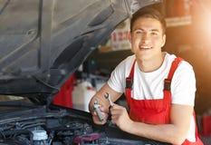 Ung automatisk mekaniker som reparerar bilen i servicemitt arkivbild