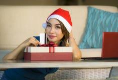 Ung avkopplad hemmastadd soffa för lycklig och härlig flicka i jultomtenhatt genom att använda bärbar datordatoren som betalar fö arkivfoto