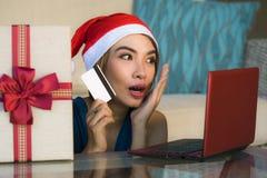 Ung avkopplad hemmastadd soffa för lycklig och härlig flicka i jultomtenhatt genom att använda bärbar datordatoren som betalar fö royaltyfri bild
