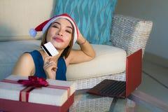 Ung avkopplad hemmastadd soffa för lycklig och härlig flicka i jultomtenhatt genom att använda bärbar datordatoren som betalar fö royaltyfri foto