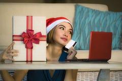 Ung avkopplad hemmastadd soffa för lycklig och härlig flicka i jultomtenhatt genom att använda bärbar datordatoren som betalar fö royaltyfria bilder