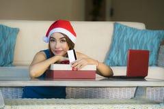 Ung avkopplad hemmastadd soffa för lycklig och härlig flicka i jultomtenhatt genom att använda bärbar datordatoren som betalar fö arkivbild