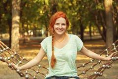 Ung avslappnande kvinna i en hängmatta utomhus royaltyfri foto