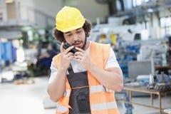 Ung bärande skyddskläder för manuell arbetare, medan genom att använda walkie-talkie i metallbransch royaltyfri foto