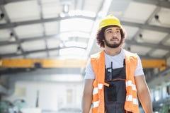Ung bärande skyddskläder för manuell arbetare som ser bort i metallbransch royaltyfri fotografi