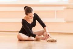 Ung balettdansör som sätter på pointeskor Arkivbild