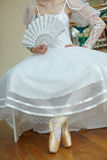 Ung ballerina i den vita klänningen som rymmer en vit fan Fotografering för Bildbyråer