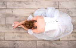 Ung ballerina i pointeskor på golvet fotografering för bildbyråer