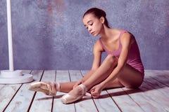 Ung ballerina som sätter på hennes balettskor Arkivfoto