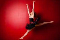 Ung ballerina som utför ett hopp mot den ljusa röda väggen Arkivbild