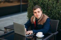 Ung bankanställd arbetar på en bärbar dator på lunchtime Arkivbilder