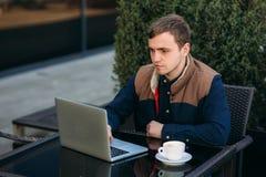 Ung bankanställd arbetar på en bärbar dator på lunchtime Royaltyfria Foton