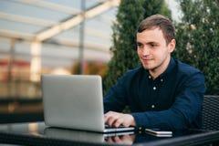 Ung bankanställd arbetar på en bärbar dator på lunchtime Fotografering för Bildbyråer