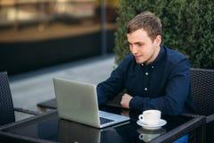 Ung bankanställd arbetar på en bärbar dator på lunchtime Royaltyfria Bilder