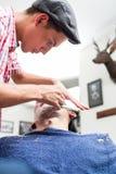 Ung barberare som rakar med den raka rakkniven arkivbild
