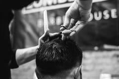 Ung barberaredanandefrisyr i barberare shoppar Arkivbild