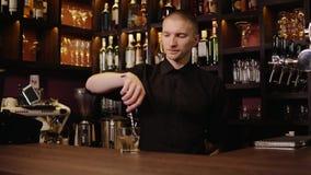 Ung bartender i hällande whisky för stånginre, i exponeringsglas och att komma med det för besökare lager videofilmer