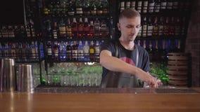 Ung bartendermixologist som sätter många kuber av isar i exponeringsglas och går att göra coctailen i härlig modern stång arkivfilmer