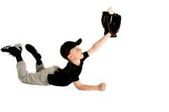 Ung basebollspelaredykning som fångar högboll Arkivbilder