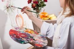 Ung begåvad kvinnamålning royaltyfri bild