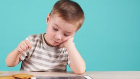 Ung begåvad pojke som studerar program på minnestavlan som isoleras på blått arkivfilmer