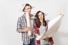 Ung bekymrad kvinna, man i tillfällig kläder som rymmer rullade ut tapetrullar Par som isoleras på vit bakgrund royaltyfri fotografi