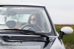 Ung beuatiful kvinna som kör en bil royaltyfria bilder