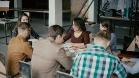 Ung blandras- grupp människor som arbetar i coworking utrymme Liten start av arkitekter som diskuterar projektidéerna stock video