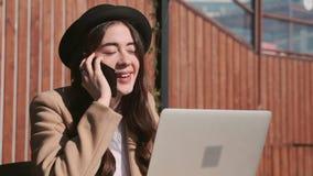 Ung blogger som talar på den utomhus- telefonen arkivfilmer