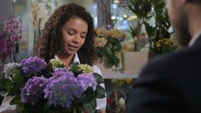 Ung blomsterhandlare som råder köpareblomningväxten arkivfilmer