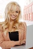Blond affärskvinna genom att använda bärbar dator på gatan Arkivfoto