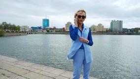 Ung blond attraktiv kvinna som går i parkera vid floden och talar på mobiltelefonen Blå skjorta, affärsdräkt arkivfilmer