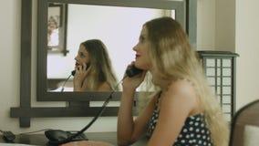 Ung blond bläddring till och med menyn i ett stilfullt hotellrum som kallar och gör därefter en beställning stock video